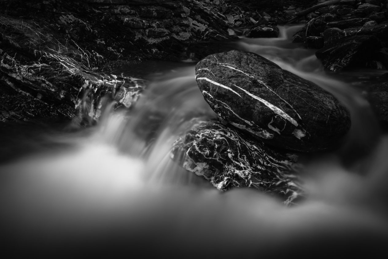 A fine art long exposure of an alpine mountain river rapid in black & white, featuring white water and dark marbled rocks with white streaks. Marbled - Copyright Johan Peijnenburg - NiO Photography