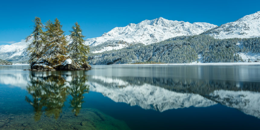 A lake landscape, featuring larch trees with fall colours and the reflection of Piz Corvatsch mountain with autumn snow at Lake Sils (Silsersee). Autumn Snow - Copyright Johan Peijnenburg - NiO Photography
