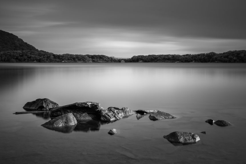 A serene and gentle dawn at Muckross Lake in B&W, with rocks in the foreground and a forest with a stone bridge in the back. Muckross Lake, also called Middle Lake or The Torc, is a lake in Killarney National Park, County Kerry, Ireland. Irish Stillness - Copyright Johan Peijnenburg - NiO Photography