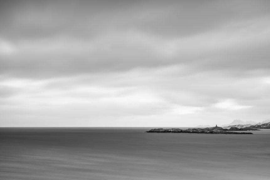 An expansive mountaintop view of the Norwegian Sea near Lofoten with a lighthouse, a coastal islands, and the mountains of Lofoten, Norway. A Norse View - Copyright Johan Peijnenburg - NiO Photography