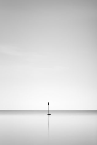 A minimalist landscape in black & white, featuring a solitary signpost and its reflection in Lac Léman (Lake Geneva). One - Copyright Johan Peijnenburg - NiO Photography