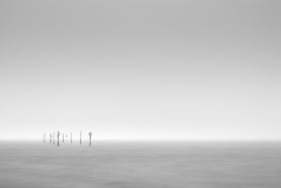 A minimalist Dutch coastal landscape in B&W with signposts at the coast of the Oosterschelde near Tholen in Zeeland on a foggy day. Passage - Copyright Johan Peijnenburg - NiO Photography