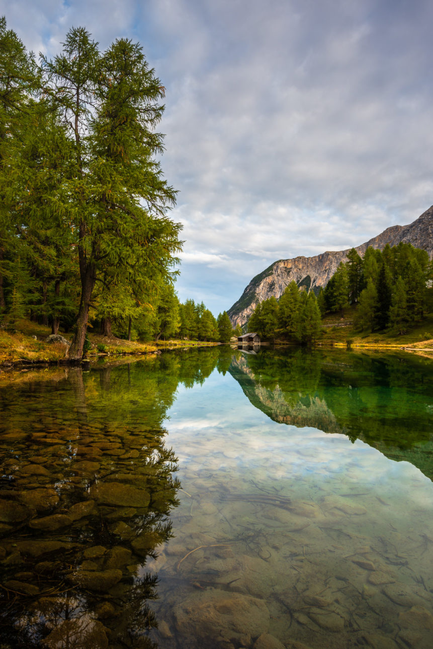 A mountain lake landscape, showing a quiet sunrise at Lai da Palpuogna in autumn with larch trees and mountains reflected in the lake. Dawning - Copyright Johan Peijnenburg - NiO Photography