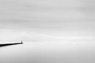 A minimalist lake landscape in black & white, showing a beacon on a jetty in Lac de Neuchâtel in Switzerland on a calm but foggy day. Misty Solitude - Copyright Johan Peijnenburg - NiO Photography
