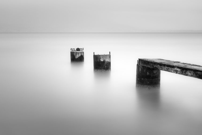A minimalist misty lake landscape in black & white, showing the remains of an abandoned pier in Lac de Neuchâtel in Switzerland. Broken - Copyright Johan Peijnenburg - NiO Photography