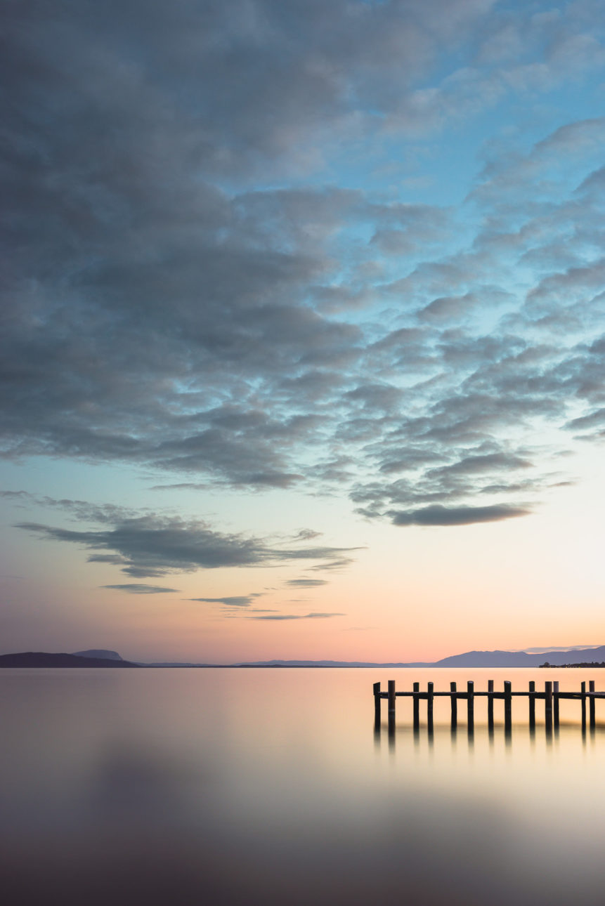 A colourful sunset with gorgeous clouds at Lac Léman (Lake Geneva), with a small wooden pier in the foreground. At the beach - Copyright Johan Peijnenburg - NiO Photography