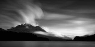 A minimalist lake landscape in B&W, showing an eruption of clouds above the Piz de La Margna and the Swiss Alps at Lake Sils in Engadin. Eruption - Copyright Johan Peijnenburg - NiO Photography