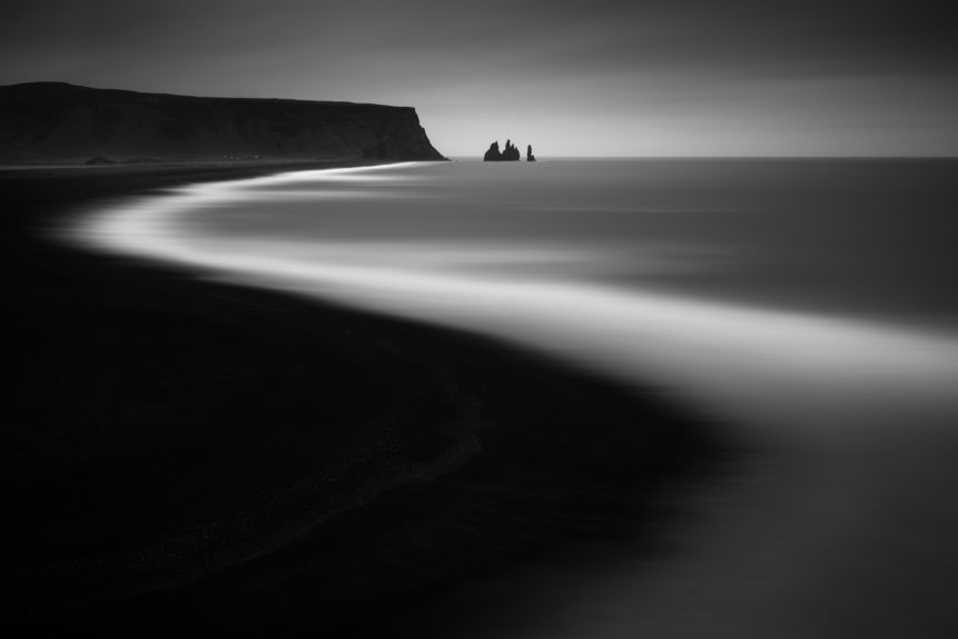 The black sand beach of Reynisfjara and the Reynisdrangar sea stacks near Vík í Mýrdal, Iceland, in black & white. Curved - Copyright Johan Peijnenburg - NiO Photography