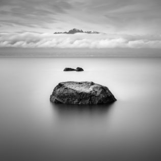 Rocks lined up as stepping stones in Lake Geneva (lac Léman) with the French Alps rising above a band of clouds, in B&W. Stepping Stones - Copyright Johan Peijnenburg - NiO Photography