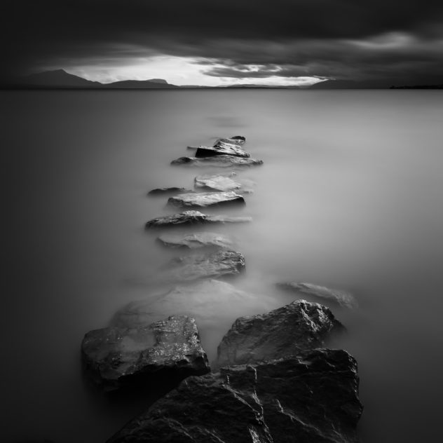 A moody lake landscape in B&W, with a line of rocks in Lac Léman (Lake Geneva) leading the eye to dark clouds and the silhouette of the Alps on the horizon. The End - Copyright Johan Peijnenburg - NiO Photography
