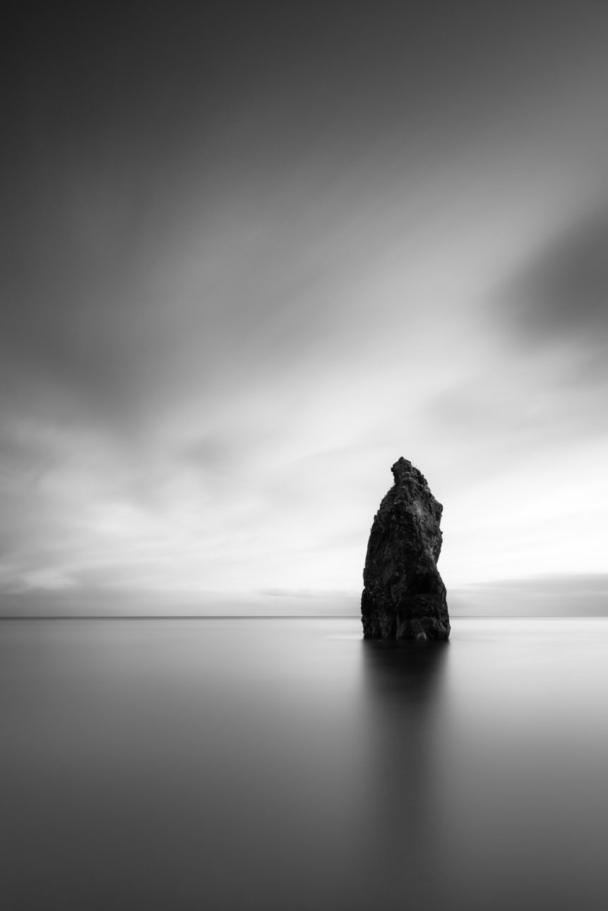 A minimalist Irish landscape in B&W, featuring a sea stack and the Celtic Sea at Ballydowane Cove in the Copper Coast Geopark, in County Waterford, Ireland. The Philosopher's Stone - Copyright Johan Peijnenburg - NiO Photography