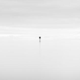 A minimalist photograph in black & white with a dreamy and soothing look and feel, featuring a signpost in Lac de Neuchâtel on a foggy and hazy day. Yield - Copyright Johan Peijnenburg - NiO Photography