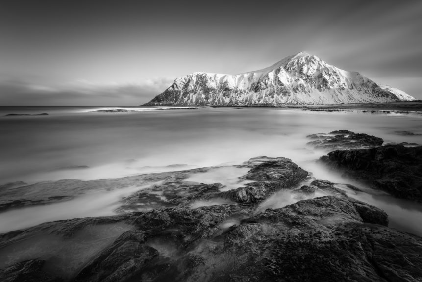 A coastal mountain landscape in B&W, showing a Skagsanden beach with Hustinden mountain in Lofoten, Norway, in winter. Nordic Sunrise - Copyright Johan Peijnenburg - NiO Photography