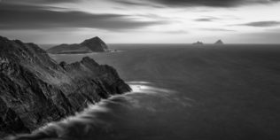 An Irish coastal landscape in B&W, showing the cliffs of Kerry and the Skellig Islands lit by the last light of sunset at the North Atlantic Ocean along the Ring of Kerry in Ireland. Last Light - Copyright Johan Peijnenburg - NiO Photography
