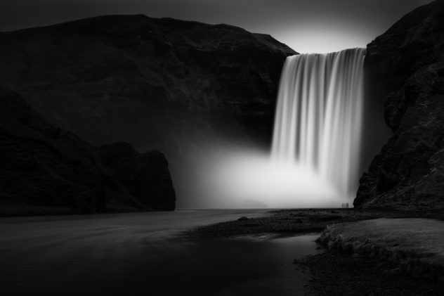 The magnificent Icelandic Skógafoss waterfall in black & white, with people standing in the spray created by the waterfall. Epic - Copyright Johan Peijnenburg - NiO Photography