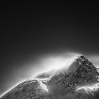 A mountain landscape in black & white, showing Piz Cambrena mountain in the Swiss Alps of Engadin enduring a snowstorm in winter. Furious - Copyright Johan Peijnenburg - NiO Photography