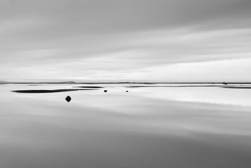 A minimalist Icelandic coastal landscape in B&W withcloud reflections on a lagoon with rocks near Stokksnes beach. Still Waters - Copyright Johan Peijnenburg - NiO Photography