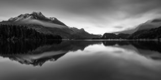 A lake landscape in black & white, featuring the mountain reflections of the Alps at sunrise in a quiet lake near Sils im Engadin, Switzerland. The main mountain in the back is Piz de la Margna. Alpine Stillness - Copyright Johan Peijnenburg - NiO Photography