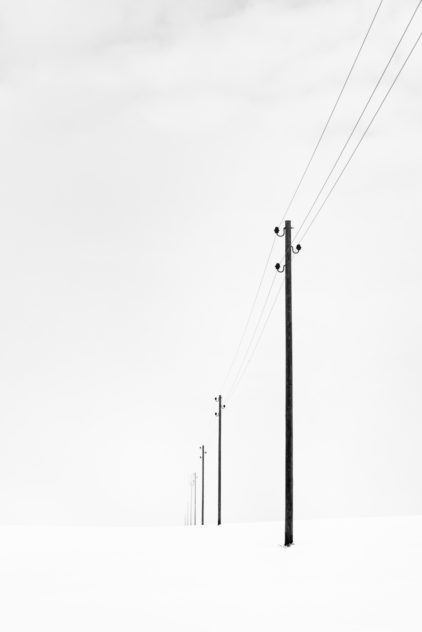 A winter landscape photograph in B&W, with telephony poles disappearing towards the horizon in a foggy and snowy Swiss winter landscape. Fading - Copyright Johan Peijnenburg - NiO Photography