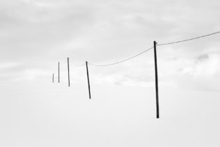 A serene minimalist winter landscape in black & white, featuring a telephony poles in the countryside with snow against a cloudy sky. Out of Sight - Copyright Johan Peijnenburg - NiO Photography