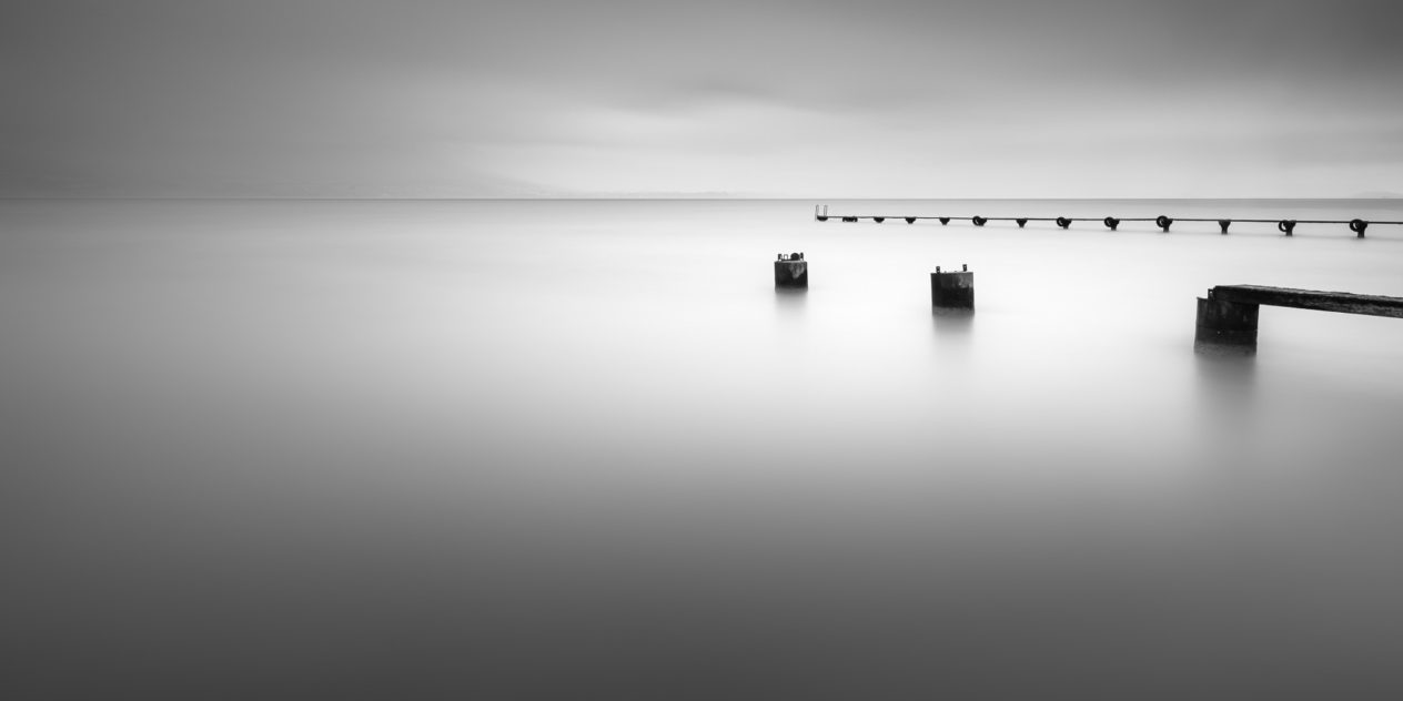 A soothing minimalist lake landscape in black & white,  with two abandoned piers in a tranquil lake ( Lac de Neuchâtel) on a foggy day. Tranquillity - Copyright Johan Peijnenburg - NiO Photography