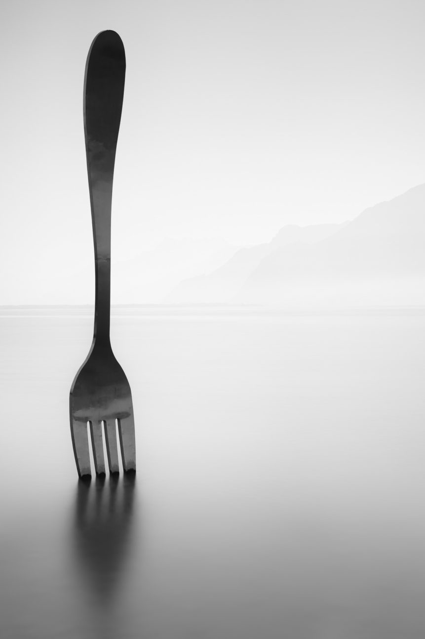 A minimalist lakeside photograph in B&W featuring a work of art in the form of a fork in the water of Lac Léman (Lake Geneva)  in Vevey in Switzerland, with the silhouette of the French Alps in the background. A tasty lake - Copyright Johan Peijnenburg - NiO Photography