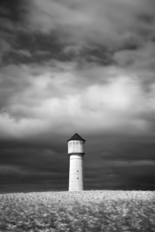 A landscape in B&W, showing a white water tower in a rapeseed flower field just before the storm in the Swiss countryside. Fearless - Copyright Johan Peijnenburg - NiO Photography