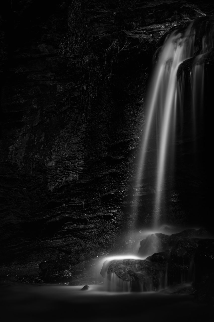 A waterfall in B&W, with water falling from a cliff on rocks. The sun subtly lights the spray of the waterfall. High Falls - Copyright Johan Peijnenburg - NiO Photography