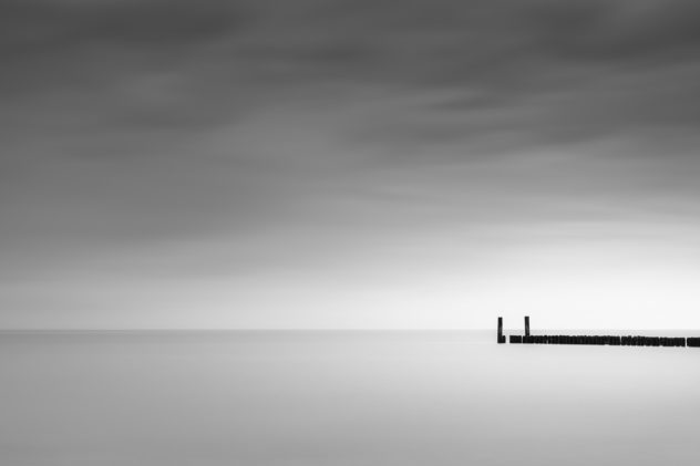 A minimalist coastal landscape in B&W with a dark sky above a breakwater in the North Sea near Domburg in Zeeland, The Netherlands. Ending silence - Copyright Johan Peijnenburg - NiO Photography