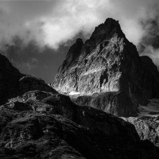 A landscape in black & white, showing clouds around the rugged peak of the Wendenhorn mountain in the Swiss Alps. Rugged - Copyright Johan Peijnenburg - NiO Photography