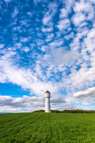 The Swiss countryside in spring, featuring a white water tower in a green field against a big blue sky with puffy clouds. Refreshing - Copyright Johan Peijnenburg - NiO Photography