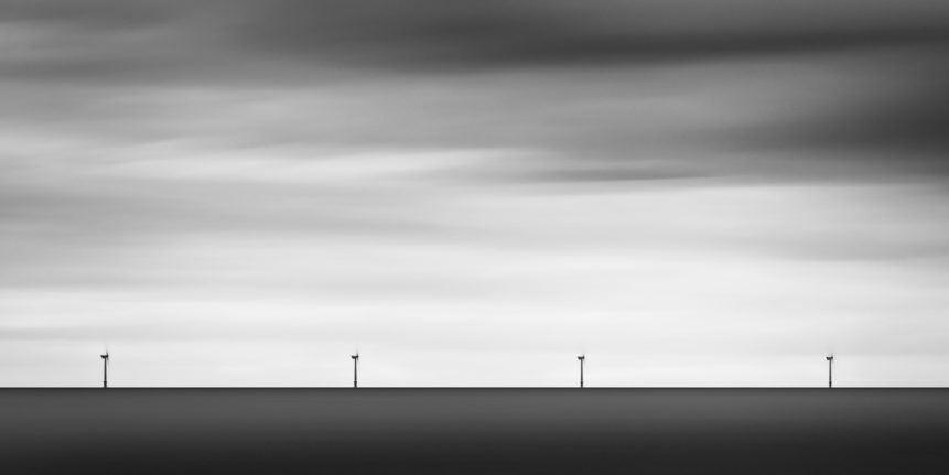 A minimalist coastal landscape in B&W, featuring four windmills (turbines) at work in the Irish Sea near Arklow in County Wicklow, Ireland. Teamwork - Copyright Johan Peijnenburg - NiO Photography