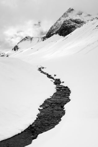 A landscape in B&W of winter in the Alps, featuring a mountain river finding its way down from the Swiss Alps near the Albula pass. Cold River - Copyright Johan Peijnenburg - NiO Photography