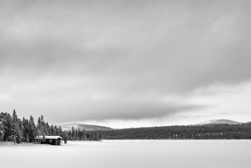 A serene and frosty winter landscape from Swedish Lapland in B&W, featuring a small cabin, a snow-covered lake, a boreal forest, hills, and a big moody sky. Frozen - Copyright Johan Peijnenburg - NiO Photography
