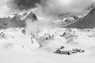 A mountain landscape in black & white, showing a small snowed-in settlement during winter in the Swiss mountains with alpine mountain peaks in the back. Snowed In - Copyright Johan Peijnenburg - NiO Photography