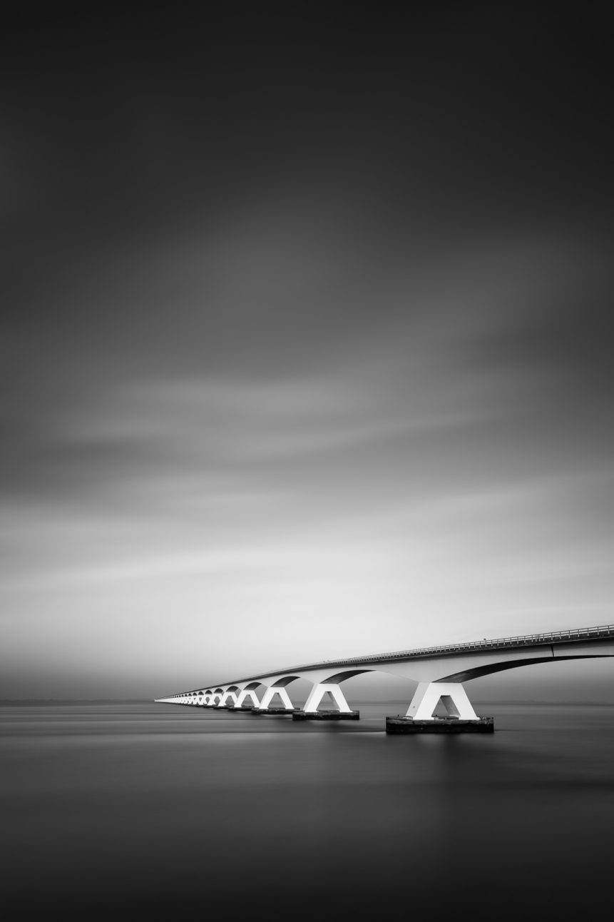 A black & white coastal landscape featuring the Zeeland Bridge (Zeelandbrug) close to sunset on a foggy day. To Infinity - Copyright Johan Peijnenburg - NiO Photography
